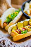 Hot Dogs with french fries in the skillet on wooden background Stock Photography