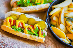 Hot Dogs with french fries in the skillet on wooden background Royalty Free Stock Photos
