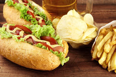 Hot dogs with glass of beer with crisps,french fries on wooden b Royalty Free Stock Photos