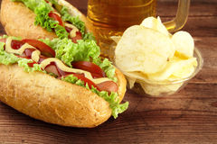 Hot dogs with glass of beer with crisps on wooden board Royalty Free Stock Photo