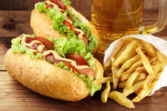 Hot dogs with glass of beer with french fries on wooden board Royalty Free Stock Photo