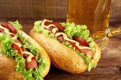 Hot dogs with glass of beer on wooden board Stock Image