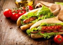 Hot-dogs grillés sur une table en bois de pique-nique Image libre de droits