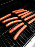 Hot Dogs on a Grill. Hot Dogs being grilled on a BBQ pit for a barbecue party Stock Photos