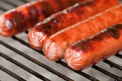 Hot dogs grilling. Four hot dogs getting nicely done on a charcoal grill Stock Images