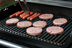Hot Dogs and Hamburgers on. A closeup of some fresh and juicy hamburgers cooking on the grill Stock Image