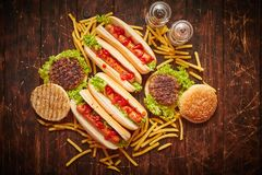 Hot dogs, hamburgers and french fries. Composition of fast food snacks royalty free stock images