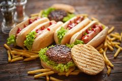 Hot dogs, hamburgers and french fries. Composition of fast food snacks royalty free stock photos