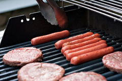 Hot Dogs and Hamburgers on the Grill. A closeup of some fresh and juicy hamburgers cooking on the grill Royalty Free Stock Photo