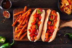 Hot dogs with hot peppers, onions and fries, flat lay on dark wood Royalty Free Stock Photos