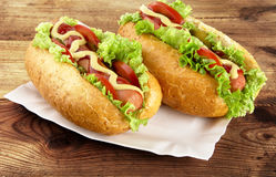 Hot dogs with lettuce,tomatoes and cucumber on tray on wooden board Stock Photo