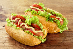 Hot dogs with lettuce,tomatoes and cucumber on wooden board Royalty Free Stock Photography