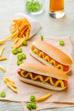 Hot dogs and beer. Hot dogs with mustard and French fries on baking paper, close-up. Hot pepper, glass of beer, wooden background. Sport fan food stock photography