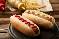 Hot dogs with mustard and ketchup. On wooden table stock photography