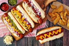 Hot dogs with potato wedges, above scene on rustic wood Royalty Free Stock Image