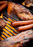 Hot dogs and ribs on a grill Royalty Free Stock Photography