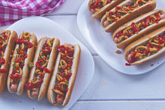 Hot dogs with roasted onion, pickled cucumber, ketchup and musta Royalty Free Stock Photos