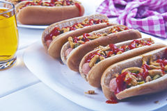 Hot dogs with roasted onion, pickled cucumber, ketchup and musta Stock Photos
