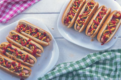 Hot dogs with roasted onion, pickled cucumber, ketchup and musta Stock Image