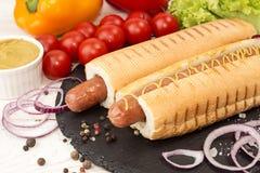 Hot-dogs sur l'ardoise noire avec des légumes Photos libres de droits