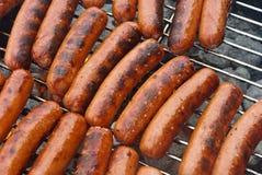 Hot-dogs sur un gril de BBQ de charbon de bois Photographie stock libre de droits