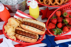 Hot Dogs on 4th of July Picnic Table. Looking down on a picnic table decorated for the 4th of July. Hot Dogs, chips, strawberries, mustard, ketchup, pretzels Royalty Free Stock Images