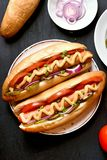 Hot dogs with tomato, marinated cucumbers, onion Stock Photos