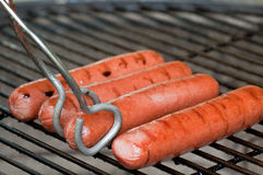 Hot dogs and tongs. Four hot dogs on a charcoal grill with tongs about to turn one royalty free stock photos