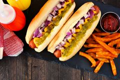 Hot dogs with onions, relish, mustard and ketchup served with fries, close up, top view table scene. Hot dogs topped with onions, relish, mustard and ketchup stock photos