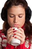 Hot Drink. Young woman drinking a hot drink from a white mug, isolated in a white background Stock Photos