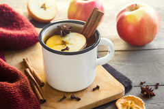 Hot drink with apples. Hot drink of apple tea with cinnamon stick, star anise and clove. Seasonal mulled wine in mug on wooden background. Hot drink with apples Royalty Free Stock Images