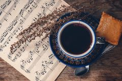 Hot drink and biscuit with musical notes and autumn leaves on a wooden table surface. Top view royalty free stock images