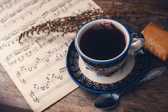Hot drink and biscuit with musical notes and autumn leaves on a wooden table surface. Top view royalty free stock photography
