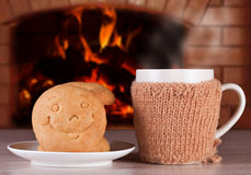 Hot drink with buns in the form of smiles to warm and positive mood. On the background of a blazing fire in the oven Royalty Free Stock Photography