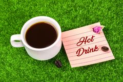Hot drink with coffee. Hot drink word in memo with coffee cup , coffee bean and dried rose bud on grass royalty free stock photo