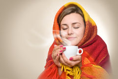 Hot drink from a cup. A young woman caught a cold, wrapped in a blanket and something hot drink from a cup stock photo