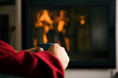 Hot drink in front of fireplace. Mature man (only hands to be seen) drinking a glass of mulled wine in front of his fireplace in the comfort of his home Royalty Free Stock Photo