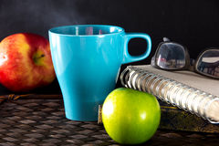 Hot drink in Light Blue  cup and apple Royalty Free Stock Photos