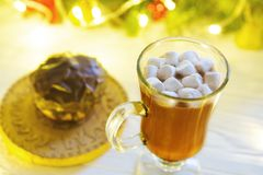 Hot drink with marshmallows on the background of Christmas decorations.  royalty free stock image