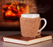 Hot drink in a mug wearing a knitted clothes, old books Stock Image