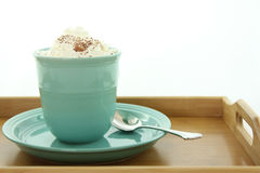A hot drink in a mug with whipped cream. A teal cup and saucer in a wooden tray with whipped cream and sprinkles.  Isolated in a white background Royalty Free Stock Photography