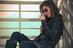 Hot drink outdoor. Young woman in cardigan and sunglasses drink coffee from paper cup on stairs, autumn day outdoor Royalty Free Stock Images