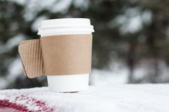 Hot drink in paper cup with snow on bright background . Royalty Free Stock Images