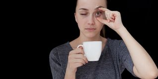 Hot drink A sleeping girl holding a cup of tea or coffee on a black background.  Stock Photos