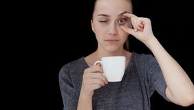 Hot drink A sleeping girl holding a cup of tea or coffee on a black background.  Stock Image