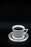 Hot drink in striped cup on the black background. Black and white minimalistic composition Stock Photos