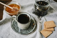 Hot drink and sweets. Cup, honey, biscuits and tea leaves over t. Ablecloth background, selective focus royalty free stock photos