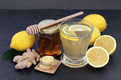 Hot Drink to Soothe a Cold. Cold and flu remedy relief drink with ginger, lemon and honey over slate background Stock Images