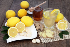 Hot Drink to Soothe a Cold. Natural cold remedy drink with vitamin c tablets, with fresh ginger, lemon, honey and cinnamon spice over oak background Royalty Free Stock Photos