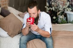 Hot drink warmth relaxation enjoyment man bed. Hot drink warmth. Relaxation and enjoyment time. Man on bed with red mug of beverage. Drinking with eyes closed stock photos